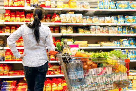 Young woman with shopping cart in the supermarket when shopping.