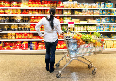 woman shopping cart: Young woman with shopping cart in the supermarket when shopping.