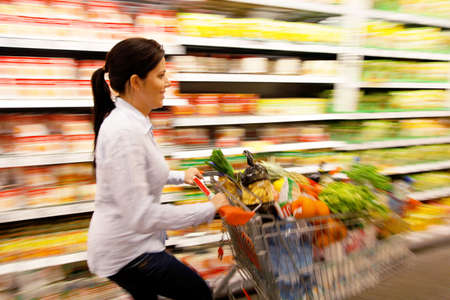 Young woman with shopping cart in the supermarket when shopping. Stock Photo - 8007496