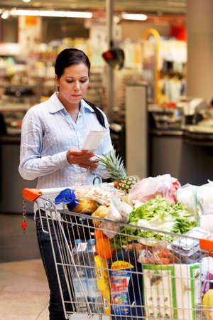 Young women controlling a slip in the supermarket Stock Photo - 8007494
