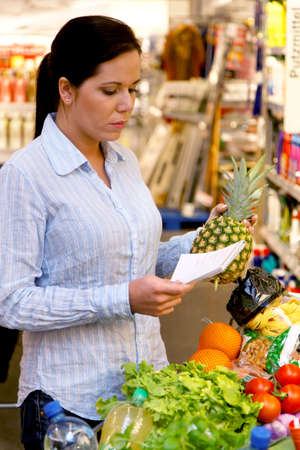 Woman with shopping list in a supermarket and shopping cart photo