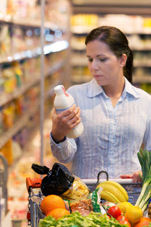 beverage display: Young woman buys in the supermarket food and fruit. Stock Photo