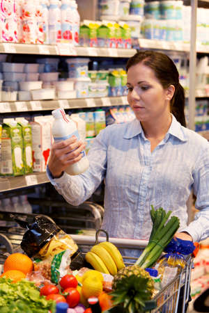 supermarket shelves: Young woman buys in the supermarket food and fruit. Stock Photo