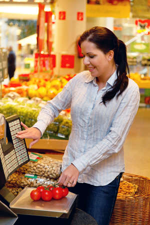 Young woman buys in the supermarket food and fruit. photo