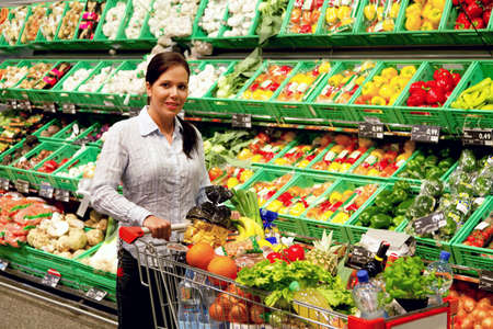 supermarket cart: Young woman buys in the supermarket food and fruit. Stock Photo