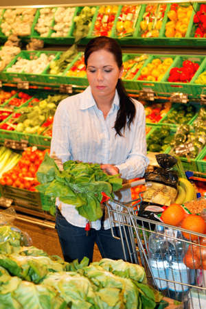 Young woman buys in the supermarket food and fruit. Stock Photo - 8007495