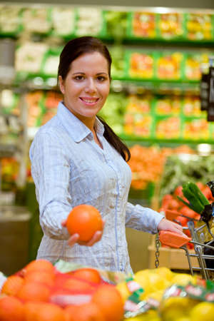 household money: Young woman buys in the supermarket food and fruit. Stock Photo