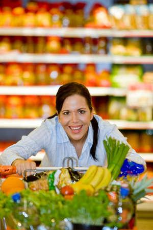 inflation basket: Joven con carrito de compras en el supermercado cuando compras.