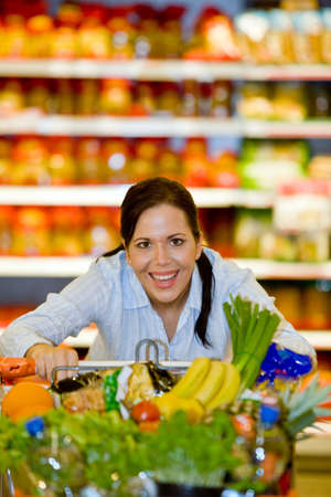 Young woman with shopping cart in the supermarket when shopping. photo