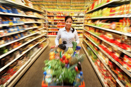 Young woman with shopping cart in the supermarket when shopping. Stock Photo - 8007487