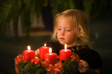 Child with Advent wreath for Christmas. 4 candles lit. photo