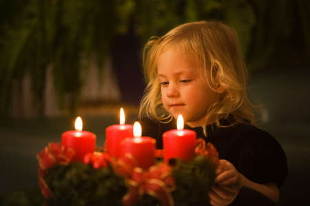 advent: Child with Advent wreath for Christmas. 4 candles lit.