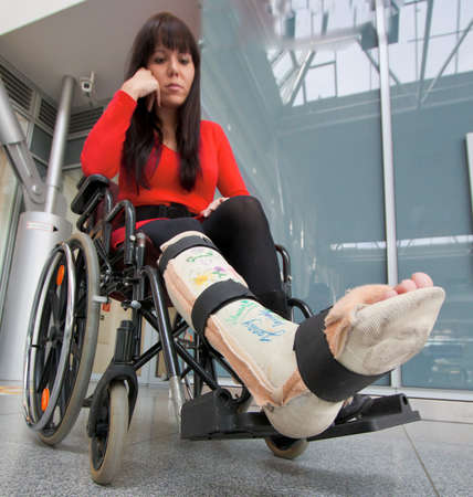 household accident: Young woman with a leg cast and wheelchair in the hospital