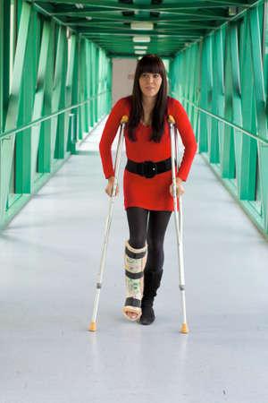 jambe cass�e: Jeune femme avec une jambe pl�tr�e et des b�quilles � l'h�pital