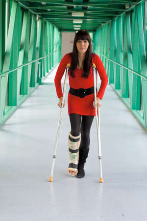 household accident: Young woman with a leg cast and crutches in hospital Stock Photo