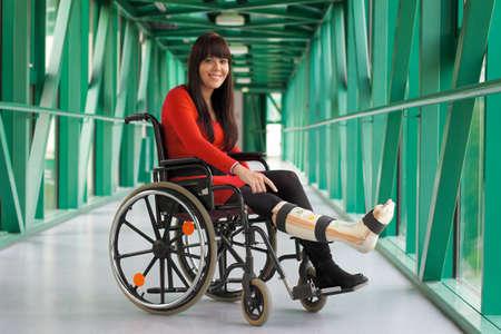 Mujer joven con un elenco de pierna y la silla de ruedas en el hospital