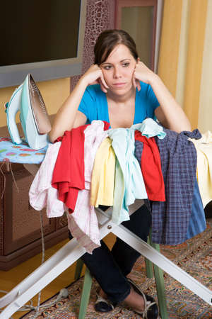 revision: Young housewife gets bored with the housework. Iron and ironing clothes. Stock Photo