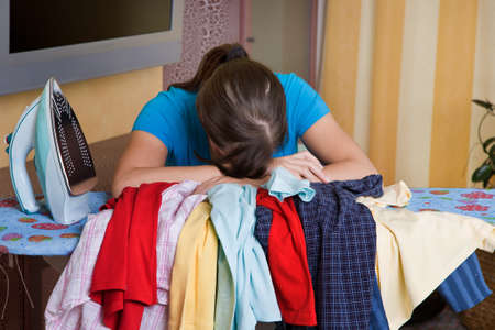 listless: Young housewife gets bored with the housework. Iron and ironing clothes. Stock Photo