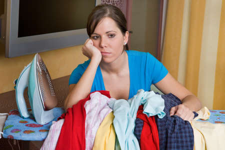 exhaustion: Young housewife gets bored with the housework. Iron and ironing clothes. Stock Photo