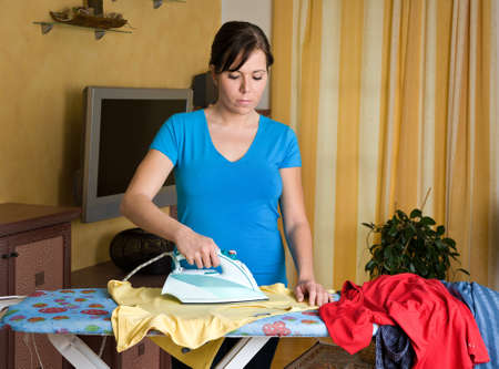 Young housewife gets bored with the housework. Iron and ironing clothes. photo
