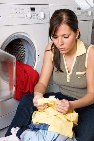 Young housewife reads the information in a garment. Washing day washing photo