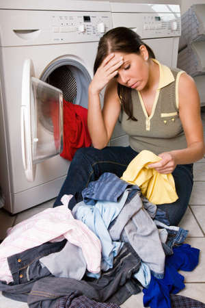 listless: Young housewife doing laundry with a washing machine. Stock Photo