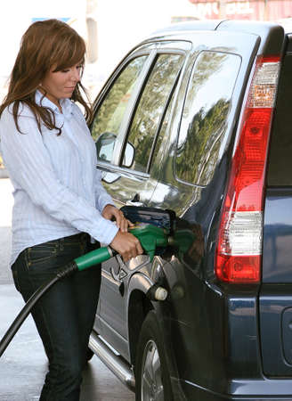 gas station: Young woman at a gas station when filling up their cars Stock Photo