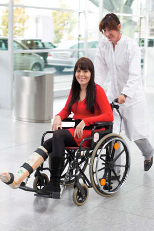household accident: Young woman with a leg cast, wheelchair and nurse Stock Photo