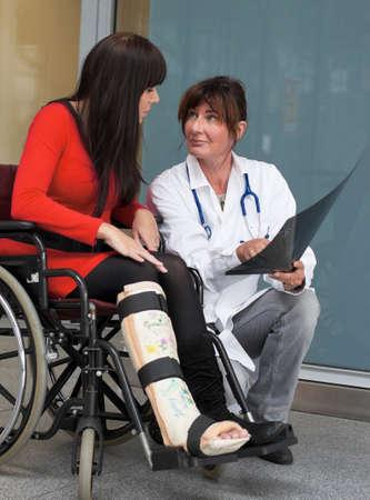 orthop�die: Jeune femme avec la jambe dans le pl�tre et m�decin dans un h�pital