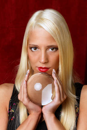 Young woman indicated the future from a crystal ball in her hands photo