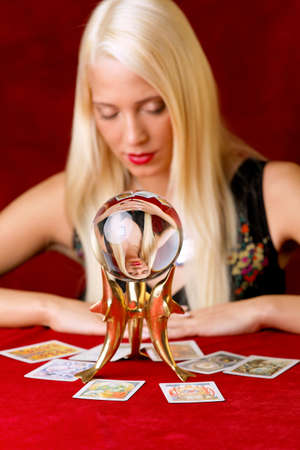 summoning: Young woman indicated the future of Tarot cards and a crystal ball