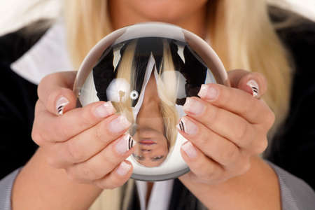 Young woman indicated the future from a crystal ball in their hands photo
