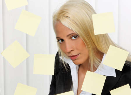 living things: Stressed-out young woman with multiple assignments memos Stock Photo