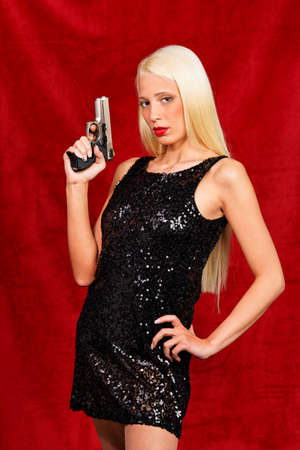 Woman in the little black dress posing with gun drawn photo