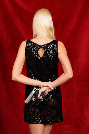Woman in the little black dress with a hidden weapon photo