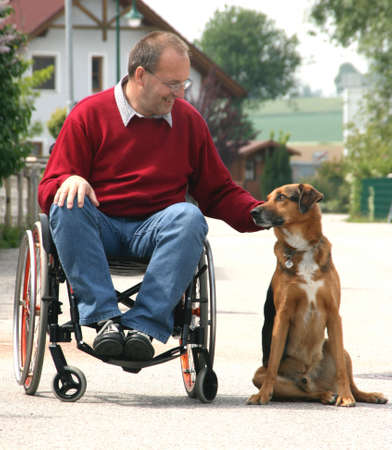 needy: Middle-aged man with a walking disability seated in a wheelchair Stock Photo