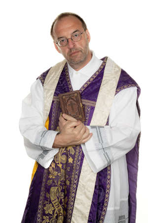 preacher: a Catholic priest with a bible in worship Stock Photo