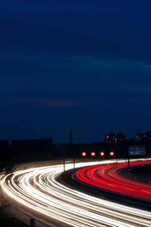 Cars at night on a highway. Rope lights and illuminated signs photo
