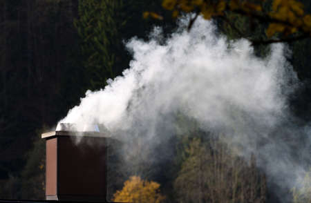 emissions: Smoking chimney of a house. Emissions and environmental protection