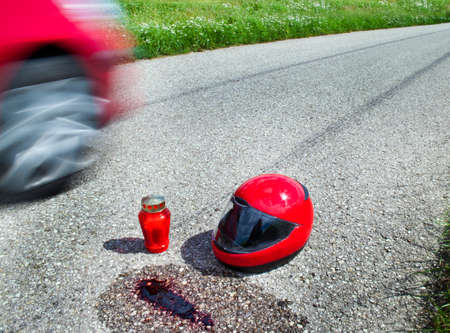 Helmet after a traffic accident on a country road. Candle and blood. Stock Photo