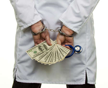 bribes: A doctor with dollar bank notes and handcuffs