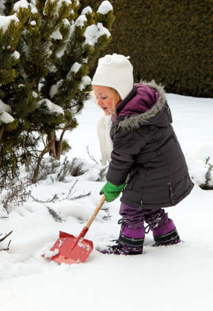 Snow shoveling snow shovel in the winter. Child with bucket photo