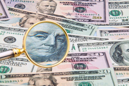 budgets: Many American dollar bills photographed with a magnifying glass Stock Photo