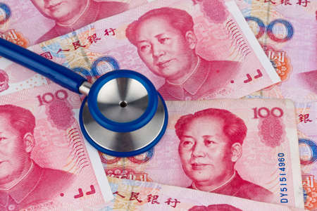 yuan: Chinese Yuan banknotes and stethoscope. Costs of health