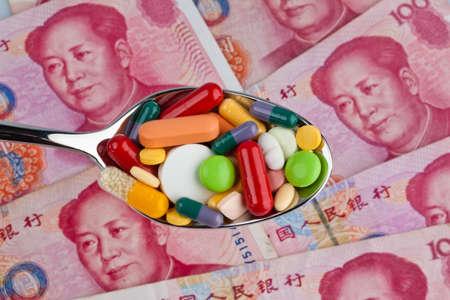 generic drugs: Yuan cinese banconote e pillole su un cucchiaio. Costi della sanit�