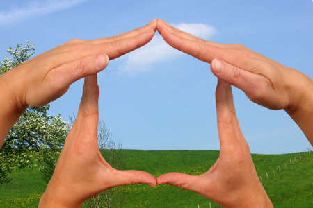 Hands, representing a house in front of a green meadow photo