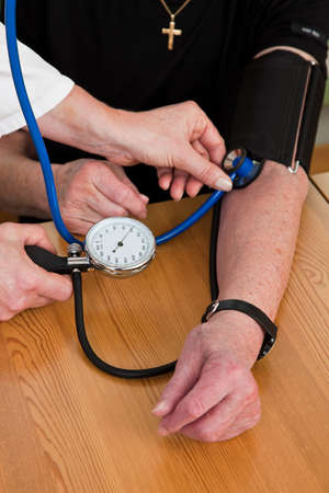 A doctor measures a patients blood pressure photo