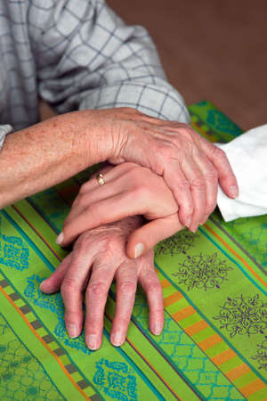 nursing association: the hands of a senior citizens held by the hand of a nurse