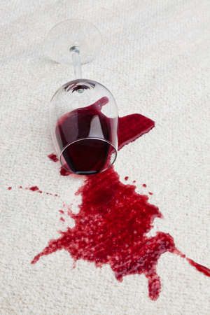 household accident: A toppled glass of red wine with a dirty carpet. Stock Photo