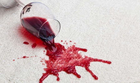 overturned overturn: A toppled glass of red wine with a dirty carpet. Stock Photo